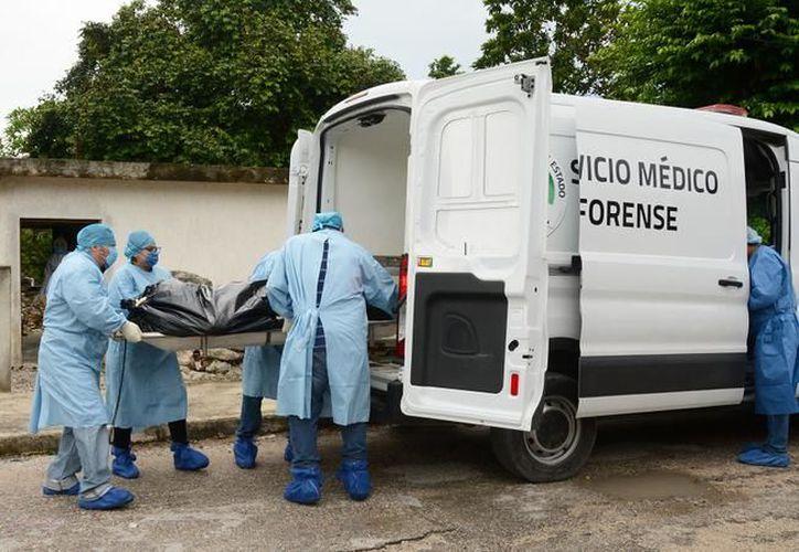 El 31 de agosto, personal del Semefo retira el cadáver de un joven suicida, en Komchén. (Foto: Milenio Novedades)