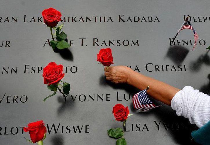 Una  mujer coloca flores sobre los nombres de la víctimas del 11 S, en la zona cero de Nueva York. Este miércoles se cumplieron 13 años de la tragedia. (AP)
