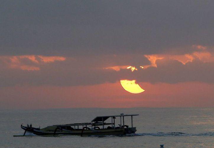 Fotografía tomada el 10 de mayo de 2013 en la que se registró un eclipse parcial de sol en una playa de Sanur, isla de Bali, Indonesia. (Archivo/EFE)