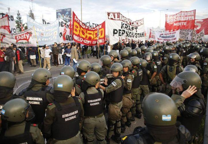 La policía antidisturbios se paran frente a los manifestantes que bloquean la carretera Panamericana que conduce a Buenos Aires. (Agencias)