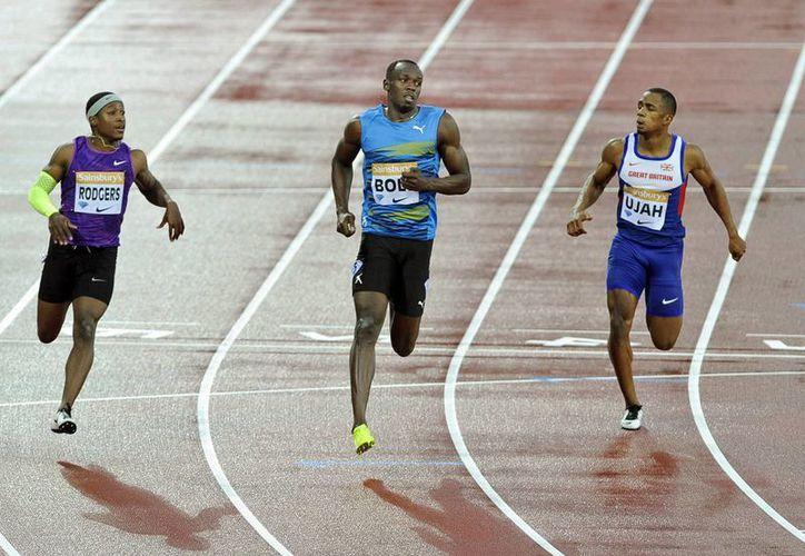 Usain Bolt (c) no tuvo rival en la carrera de 100 metros planos en Londres, dentro de la Liga Diamante. (EFE)