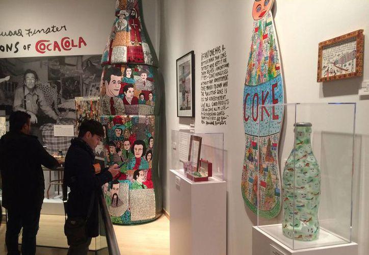 """Turistas toman fotografías en The Hihg Museum of Art de Atlanta donde se expone """"La botella Coca-Cola : Un ícono americano a 100 """" en el marco de las celebraciones del centenario de su icónica botella de cristal """"Contour"""". (EFE)"""
