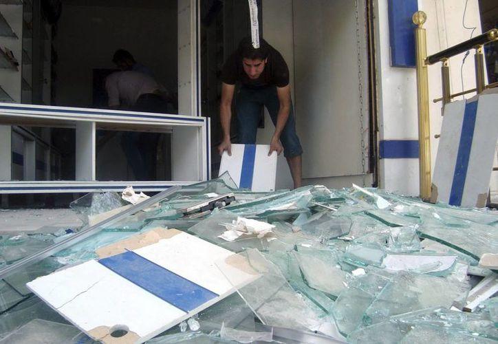 Un ciudadano iraquí recoge restos de cristales donde se produjo la explosión de un artefacto  en el céntrico barrio de Al Karrada de Bagdad, en mayo. (EFE/Archivo)