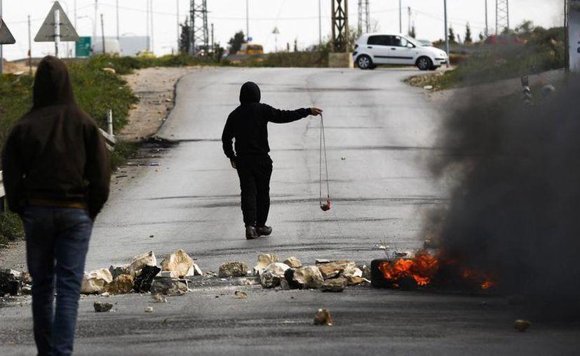 Durante la redada del Ejército israelí se detuvo a dos miembros de la organización fundamentalista Hamas. Imagen de varios palestinos lanzan piedras contra el ejército israelí durante una protesta en el campo de refugiados de Yalazón, Cisjordania, el pasado mes de marzo. (EFE/Archivo)