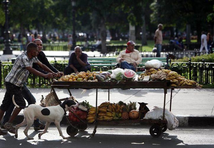 Dos hombres empujan una carretilla con frutas y vegetales, por una calle de La Habana, donde hoy inician conversaciones Cuba y EU. (Foto: EFE)