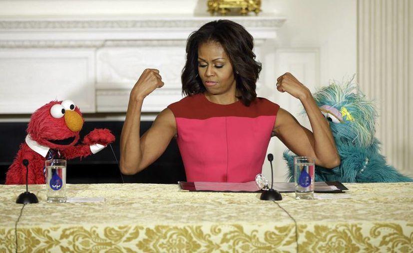 """Michelle Obama flanqueada por Elmo y Rosita, personajes de Plaza Sésamo, durante la presentación de su programa """"Movámonos"""", en el comedor de la Casa Blanca. (AP)"""