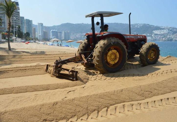 Con maquinaria pesada se intenta devolver la arena que removió el mar de fondo en las costas de Guerrero. (Notimex)