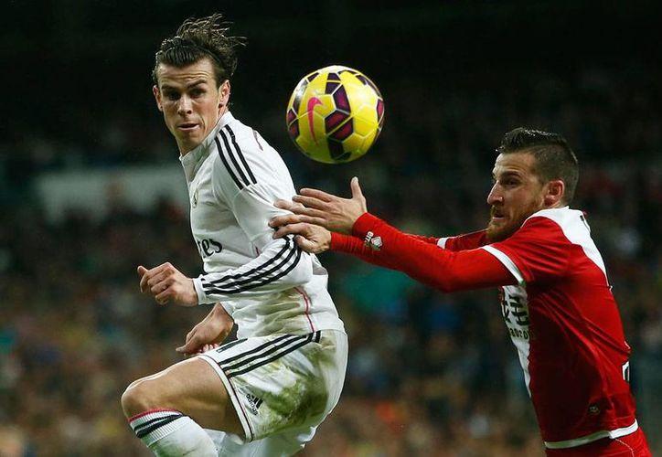 Real Madrid goleó al Rayo Vallecano, en partido de la jornada 11 del futbol español. En la imagen, Gareth Bale, auto de uno de los 5 goles de los merengues, disputa el balón con Tito, del Rayo Vallecano. (The Associated Press)