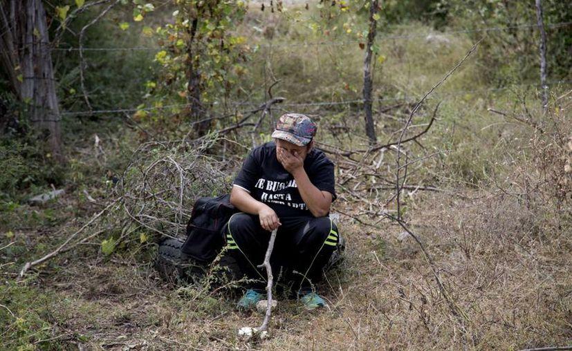Una mujer con una camiseta en la que puede leerse 'Hijo, mientras no te entierre, te seguiré buscando', descansa en una colina mientras busca a sus familiares desaparecidos en las afueras de Iguala, Guerrero. (Agencias)