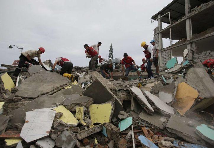 Naciones europeas y de América Latina se solidarizaron con Ecuador por el terremoto que azotó a ese país, la noche del sábado. Hombres ayudan al rescate de las personas atrapadas entre los escombros. (AP)