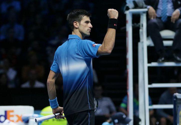 Novak Djokovic reafirmó su condición de líder mundial al vencer a Kei Nishikori en el inicio de la Copa de Maestros 2015. (AP)
