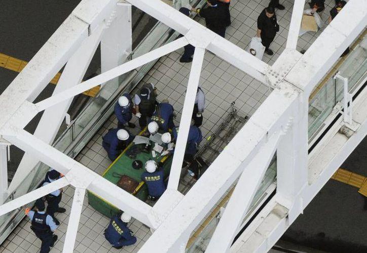 Investigadores y bomberos en la escena donde se inmoló un hombre en un paso peatonal en el Metro de Tokio. (AP Photo/Kyodo News)