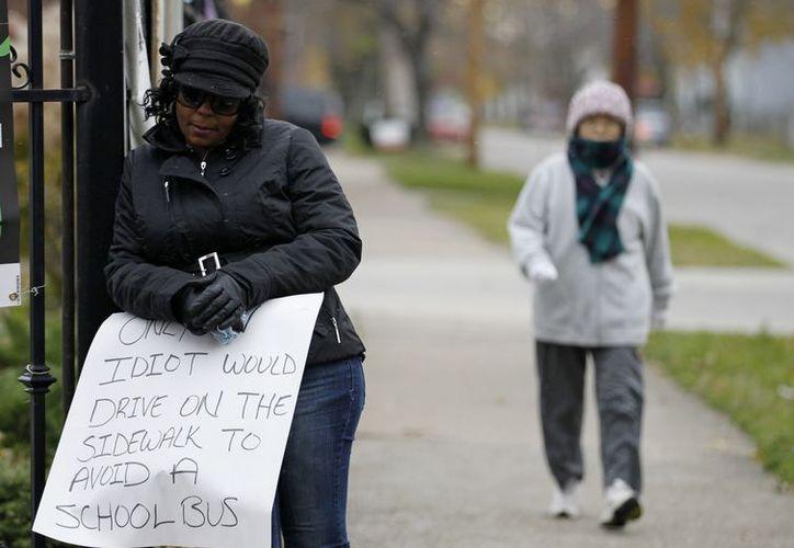 """El cartel que mostró la mujer decía: """"Sólo un idiota conduce sobre la acera para rebasar a un autobús escolar"""". (Agencias)"""