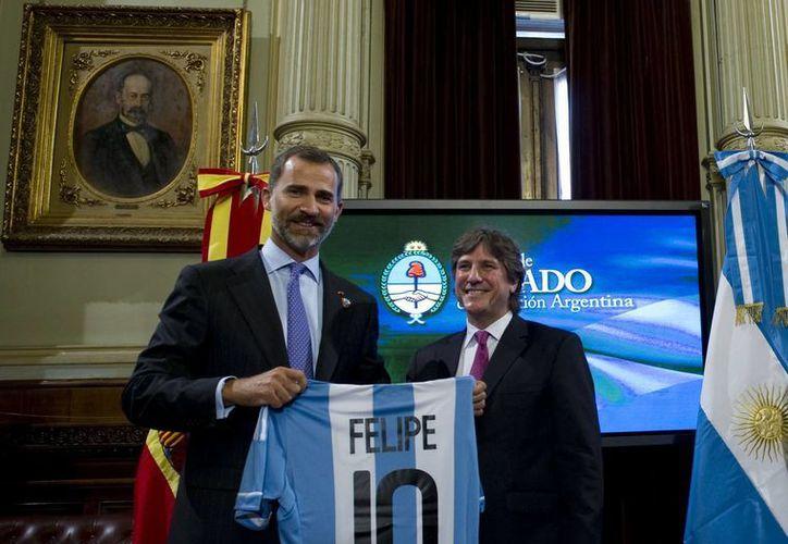 El Príncipe Felipe (i) posa con una camiseta de la selección argentina, junto con el vicepresidente de Argentina, Amado Boudou, en el marco de la candidatura de Madrid para los JO2020. (Agencias)