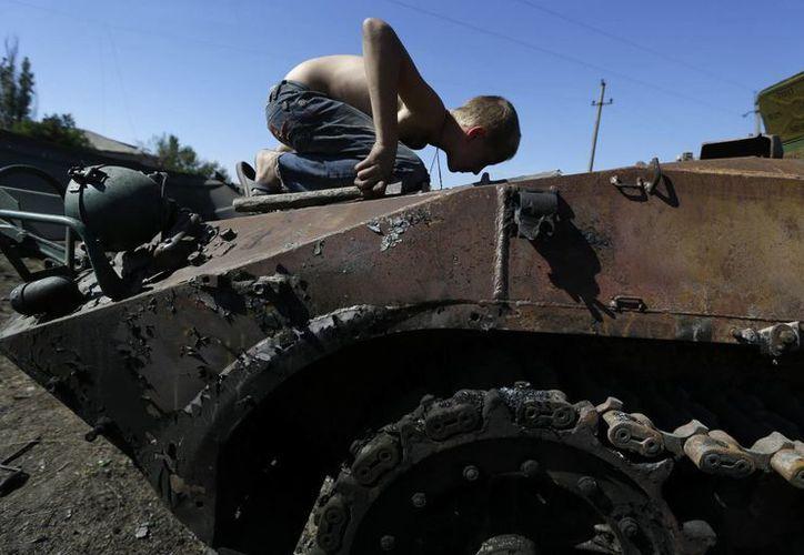 Un niño inspecciona un vehículo blindado quemado en la villa de Hrabske, en el este de Ucrania. (Agencias)