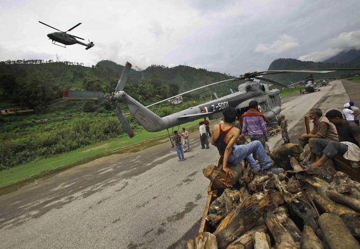 Residente de Gauchar, estado de Uttarakhand, observan la maniobra de un helicóptero de la Fuerza Aérea en la zona afectada por inundaciones. (AP)