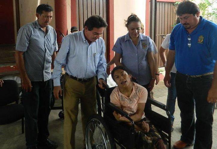 Acompañado de funcionarios municipales de Buctzotz, el senador Daniel Ávila entrega una silla de ruedas. (SIPSE)