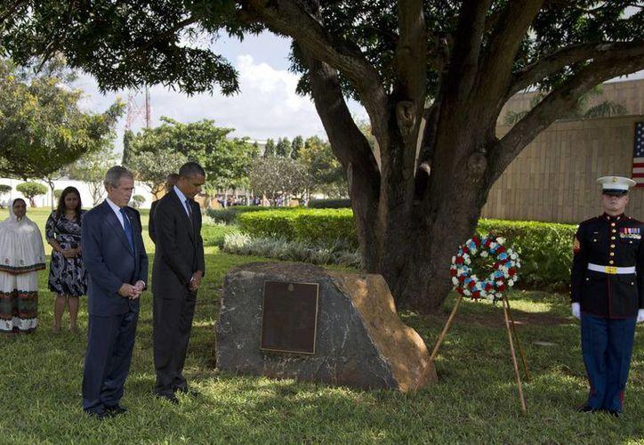 El presidente Barack Obama y el expresidente George W. Bush observan mientras un infante de Marina coloca el una corona de flores en honor de las víctimas. (Agencias)