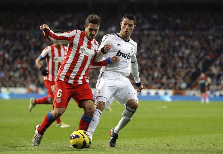 Cristiano Ronaldo y el alemán Mesut Ozil dieron los goles del triunfo sobre el Atlético. (Agencias)