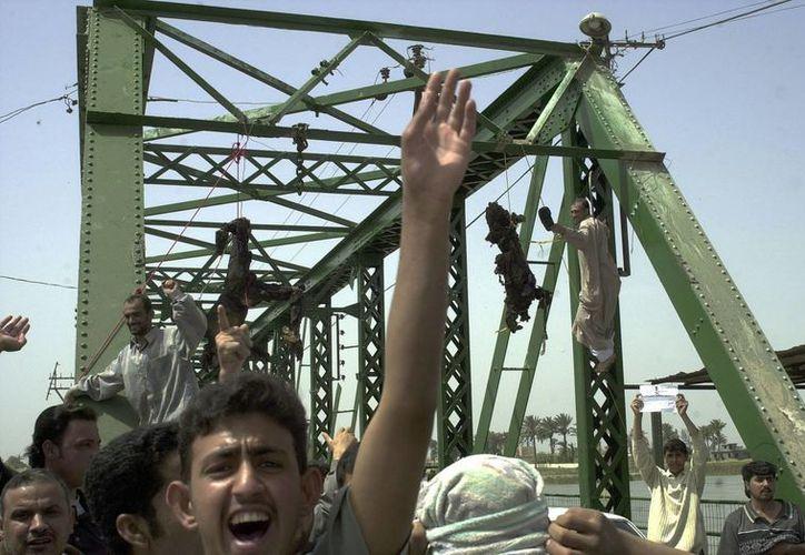 Una muchedumbre grita consignas antiestadounidenses ante los cadáveres carbonizados de dos contratistas de esa nacionalidad muertos en Faluya, Irak. (Archivo/agencias)