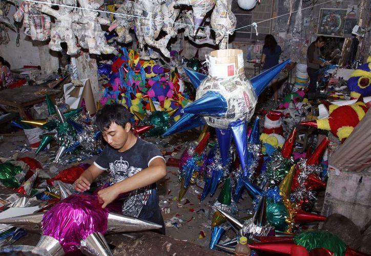 Con esmero, los artesanos elaboran llamativas piñatas que serán utilizadas en los festejos decembrinos. (Theani Ruz/SIPSE)