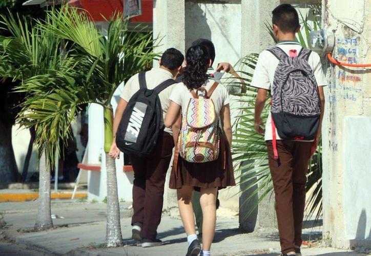 Es importante que los alumnos sean apoyados por sus padres o tutores. Imagen de tres estudiantes caminando por la calle. (Milenio Novedades)