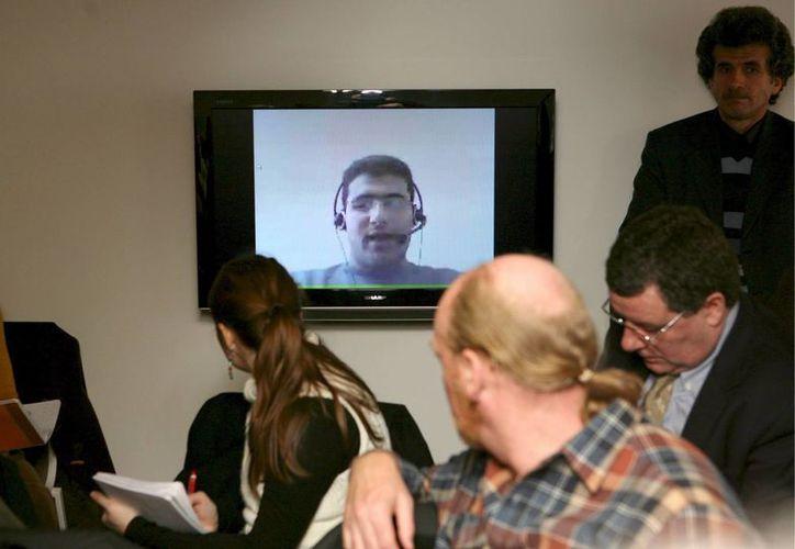 Periodistas siguen por videoconferencia las declaraciones de Mohammed Abdallah, hijo del periodista sirio detenido Ali Abdallah. (EFE)