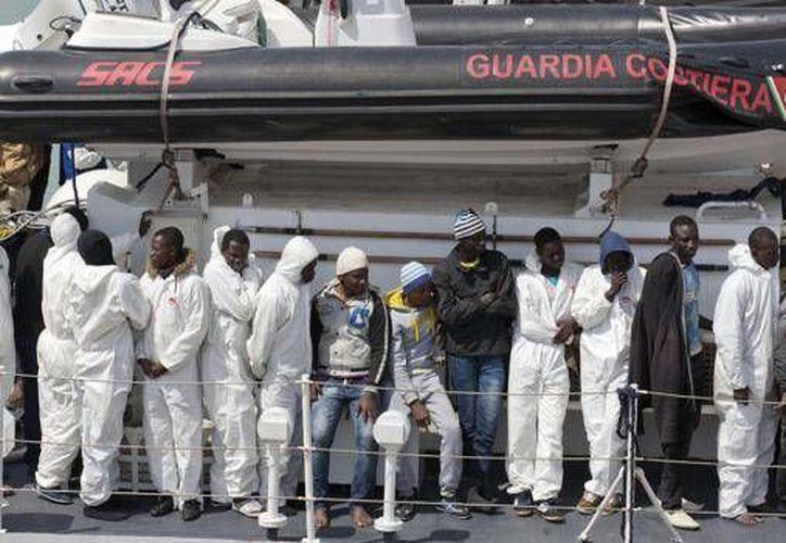Inmigrantes esperan desembarcar del navío Fiorillo de la Guardia Costera italiana en la bahía de Catania, Sicilia, en el sur de Italia. (Agencias)