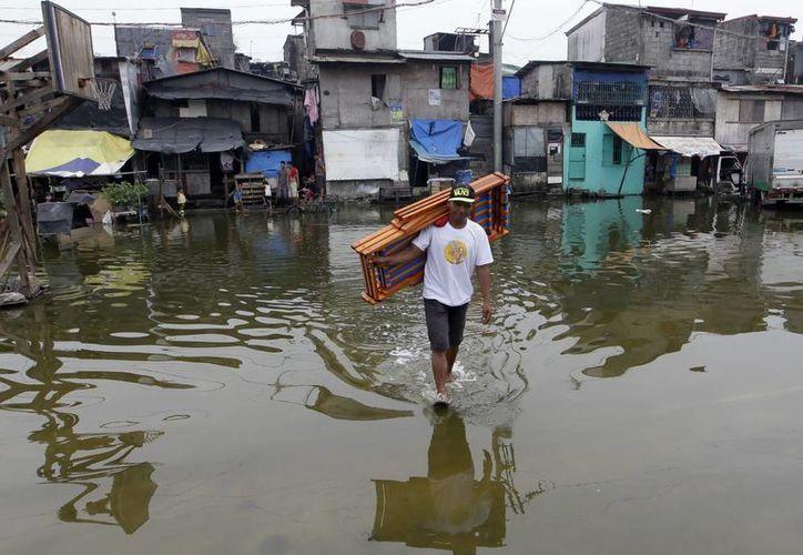 Un residente filipino camina por una calle inundada en la ciudad de Navotas, al norte de Manila. (EFE)