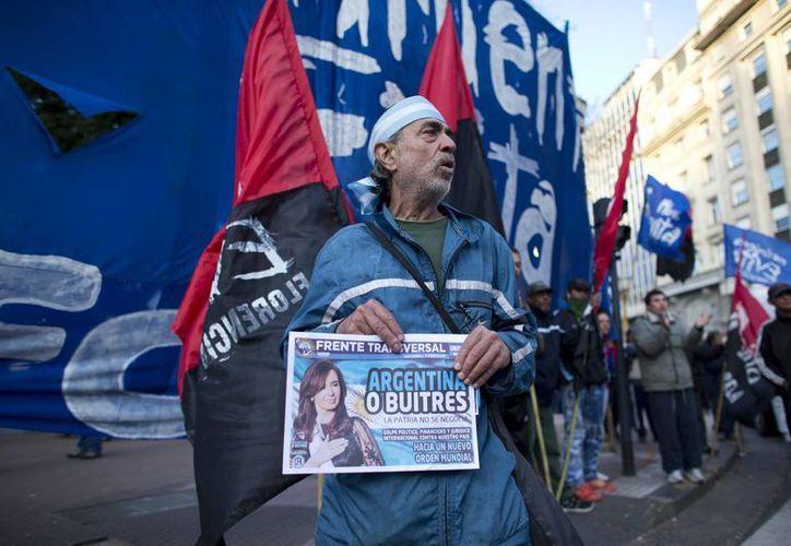 Un activista que sostiene un periódico canta el himno argentino durante una manifestación de apoyo al Gobierno que enfrenta una crisis con sus acreedores extranjeros. (Foto: AP/Victor R. Caivano)