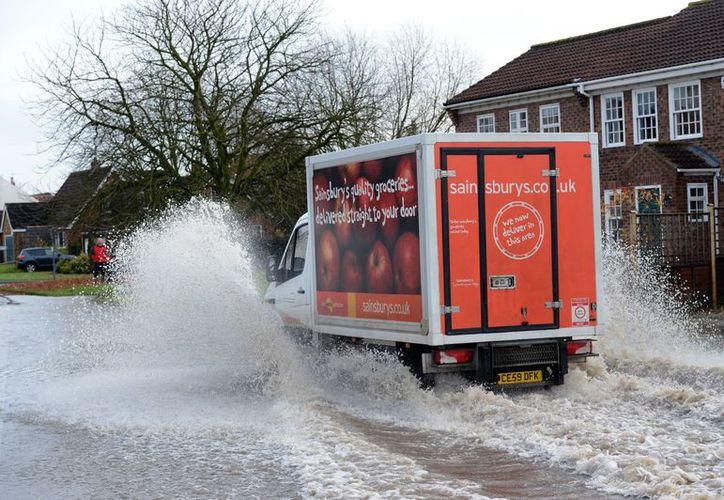 Una furgoneta de supermercado surca aguas en una calle de Appleton Roebuck, al norte de Inglaterra. (Agencias)