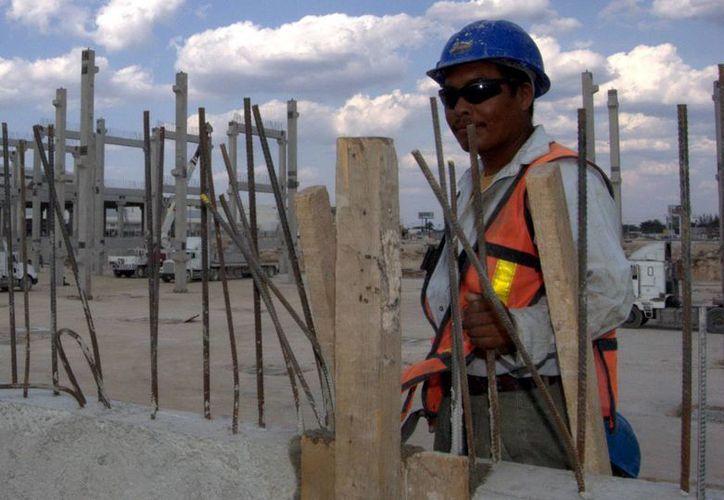 Los salarios mínimos profesionales son aquellos que definen ciertas ramas específicas de la actividad laboral, de acuerdo con habilidades del trabajador en coordinación con las áreas del sector productivo. Imagen de un obrero en una construcción en Mérida. (Milenio Novedades)