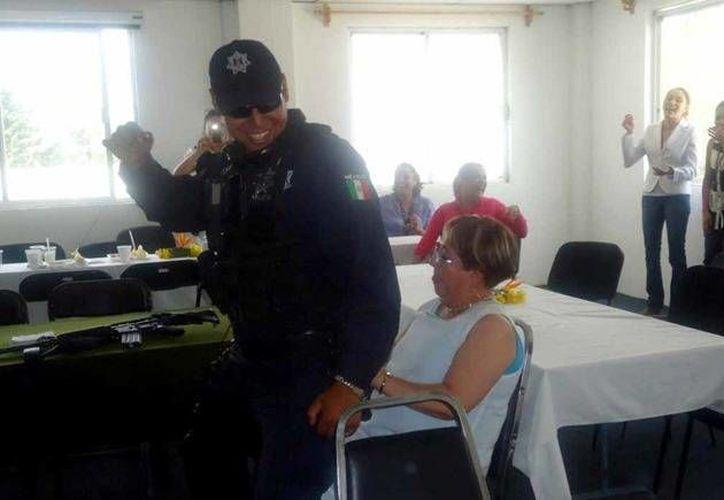 El policía municipal, armado, bailando para la subprocuradora de Justicia de Zitácuaro. (Captura del video subido a YouTube por Esquema)