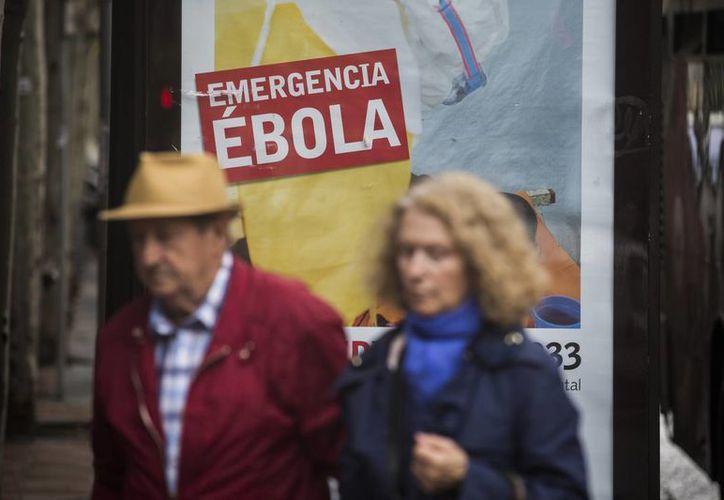 Una pareja camina cerca de un anuncio donde se pide ayuda financiera para luchar contra el ébola en África. (Agencias)