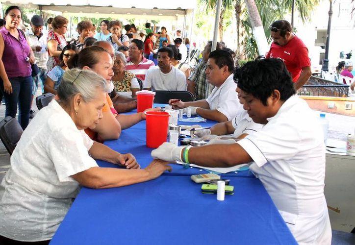 En las ferias de la salud se realizan en la Plaza Grande la población se puede realizar pruebas rápidas de azúcar, trigliceridos y colesterol. Imagen de un enfermero al realizar un test a una ciudadano. (Milenio Novedades)