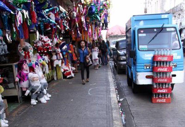 Trabajadores de Ayuntamiento delimitaron las zonas de venta en las aceras de la calle 65 entre 54 y 56, unas de las más concurridas por peatones y vehículos, en especial en estos días. (Milenio Novedades)