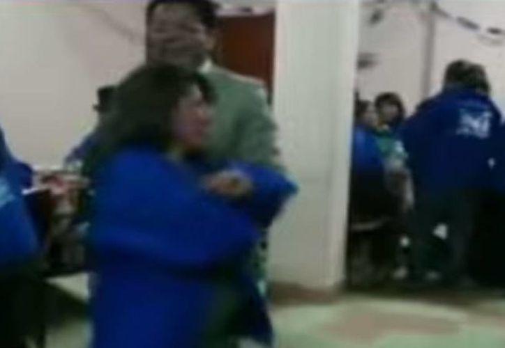 Imagen del video en donde el vocal del  Tribunal Supremo Electoral, Ramiro Paredes, baila con una de las militantes del Movimiento Al Socialismo (MAS), partido de gobierno.(Captura de pantalla de YouTube)