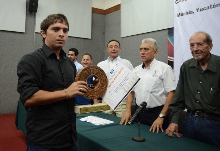 El GM cubano Lázaro Bruzón con los reconocimientos que lo acreditan como ganador en la categoría magistral del XXV torneo de  ajedrez <i>Carlos Torre Repetto</i>. (Milenio Novedades)