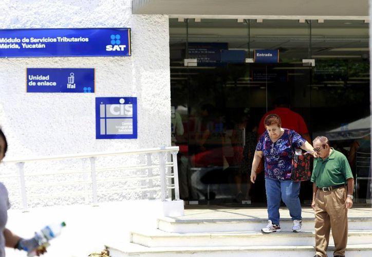Imagen de dos personas saliendo de las instalaciones del SAT en Mérida. (Milenio Novedades)