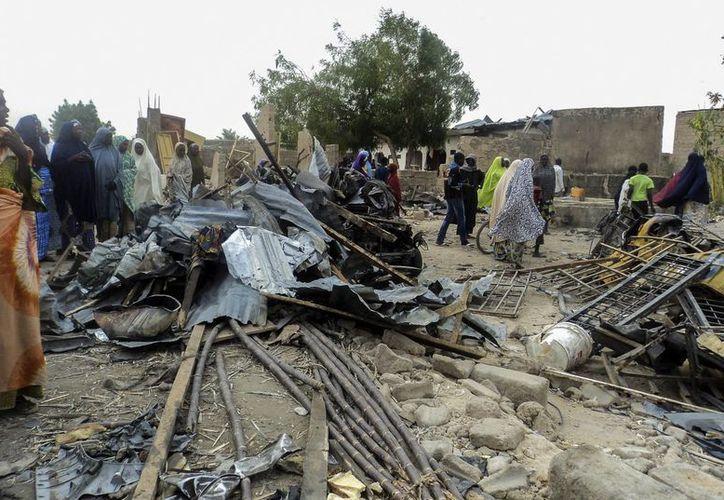 Fotografía que muestra a varias personas observando el lugar donde se produjo un atentado el día de ayer en el mercado de Binta Suga en Maiduguri, Nigeria. (EFE)