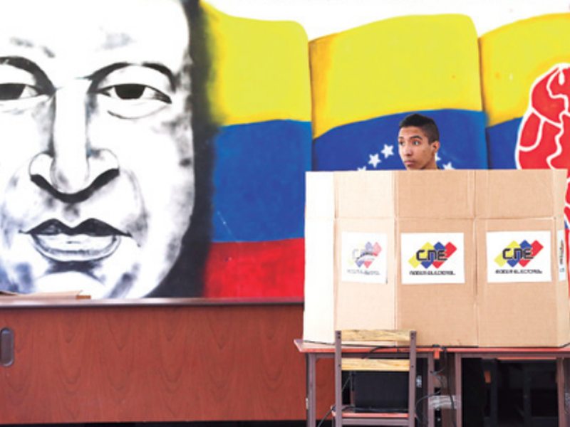 A voter chooses his candidate next to a mural of late Venezuelan President Hugo Chavez during presidential elections in Caracas, Venezuela. (AP)