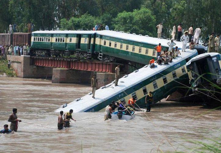 Miembros de las fuerzas de seguridad trabajan en el rescate de los pasajeros de un tren que descarriló y cayó a un canal cerca de Gujranwala, a 80 kilómetros al norte de Lahore, Pakistán. (EFE)