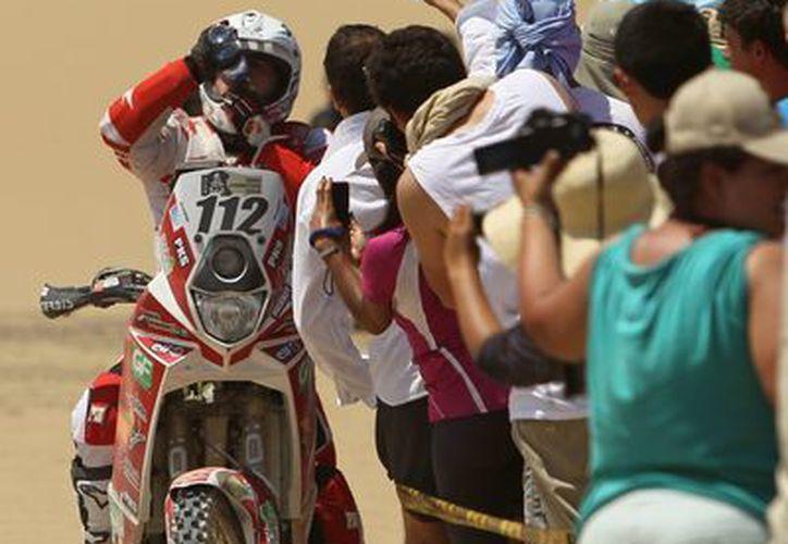 Un espectador asiste con agua al motociclista frances Yannick Guyomarch, durante la segunda etapa del rally Dakar 2013, en Pisco. (EFE)