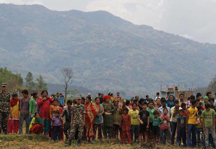 Aldeanos nepaleses esperan que baje un helicóptero de la India con ayuda para las víctimas del terremoto en Trishuli, Nepal. (Foto AP/Altaf Qadri)