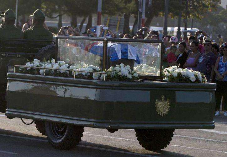 Colocadas en una pequeña urna cubierta por una bandera cubana, las cenizas del líder cubano Fidel Castro son conducidas por las calles del puerto de La Habana. (AP/Enric Marti)