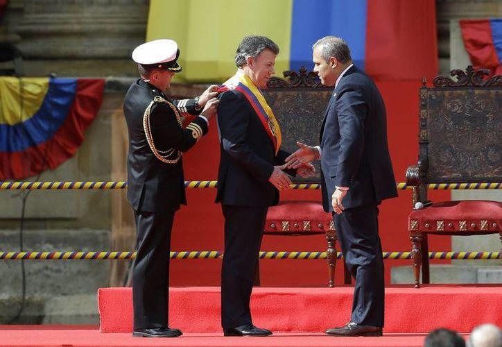 El presidente del Congreso, Jose David Name, felicita a Juan manuel Santos mientras un ayudante le coloca la banda presidencial, hoy en Bogotá, Colombia. (Foto: AP)