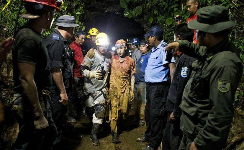 Un minero rescatado es acompañado por trabajadores de emergencia al salir por su propio pie de la mina de oro y plata El Comal en Bonanza, Nicaragua. (Agencias)