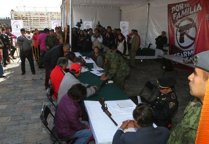 La gente acude a la explanada de la Basílica de Guadalupe a intercambiar sus armas de fuego por juguetes, laptops y apoyos económicos. (Notimex)