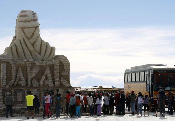 Un grupo de turistas fue registrado este sábado la visitar una escultura gigante del Dakar, hecha con piezas de sal, en el salar de Uyuni en Bolivia. (EFE)