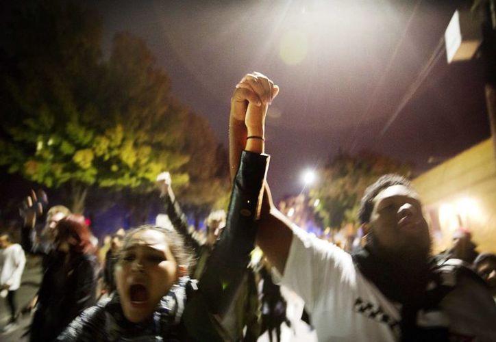 Manifestantes se agarran de las manos durante una marcha callejera para protestar por la elección de Donald Trump como presidente de Estados Unidos, en Atlanta. (AP/David Goldman)